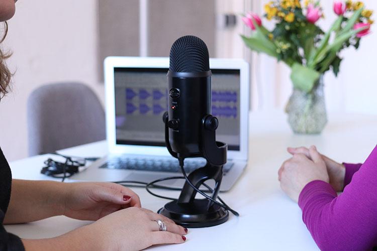 Een journalist interviewt haar gesprekspartner en neemt het gesprek op.