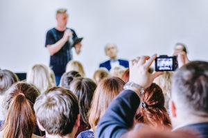 Een man geeft een speech voor een groep mensen in een zaal.