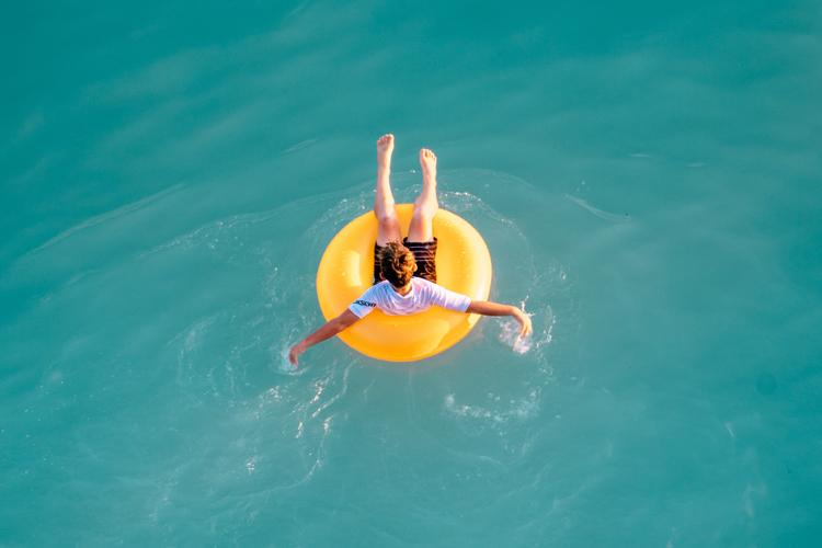 Jongen drijft op een gele band in zee.